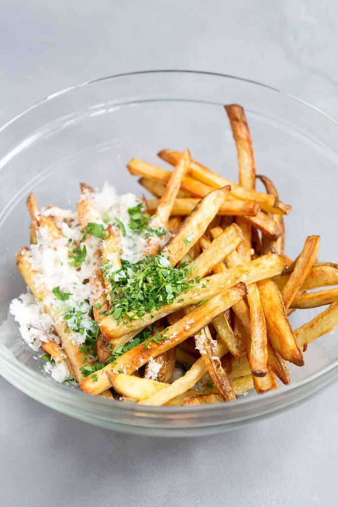 Baked French fries in a glass bowl with parsley and Parmesan cheese