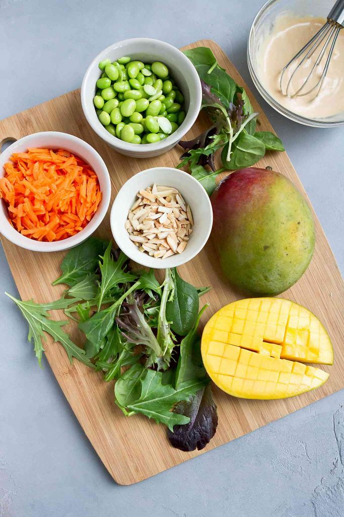Mixed greens, edamame, mango, cucumber, almonds and carrots on a bamboo cutting board