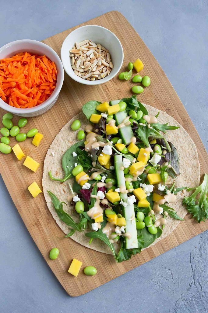 Tortilla on a cutting board, topped with vegetables, mango and goat cheese