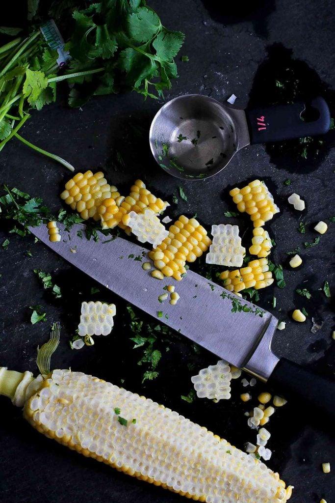 Cutting corn off of an ear of corn.