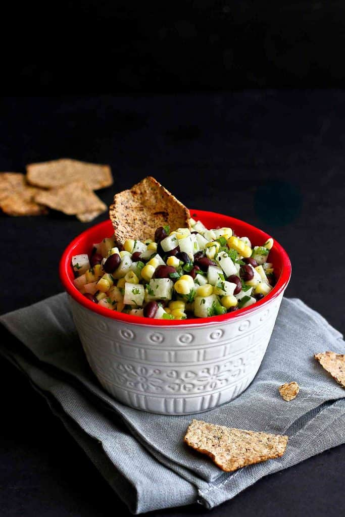 Fresh, crunchy and addictive! This jicama, black bean and corn salsa is great as a healthy, low calorie snack or served over grilled chicken or fish. 36 calories and 0 Weight Watchers SP | Recipe | Easy | Dip | Mexican | Fresh | Vegan | Gluten Free | Plant Based | Tailgating | Super Bowl #veganappetizers #superbowl #veganrecipes #cornsalsa #tailgating #cleaneating #weightwatchers #plantbased
