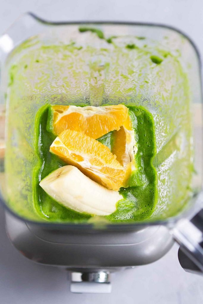 Blended spinach, half banana and orange segments in a blender