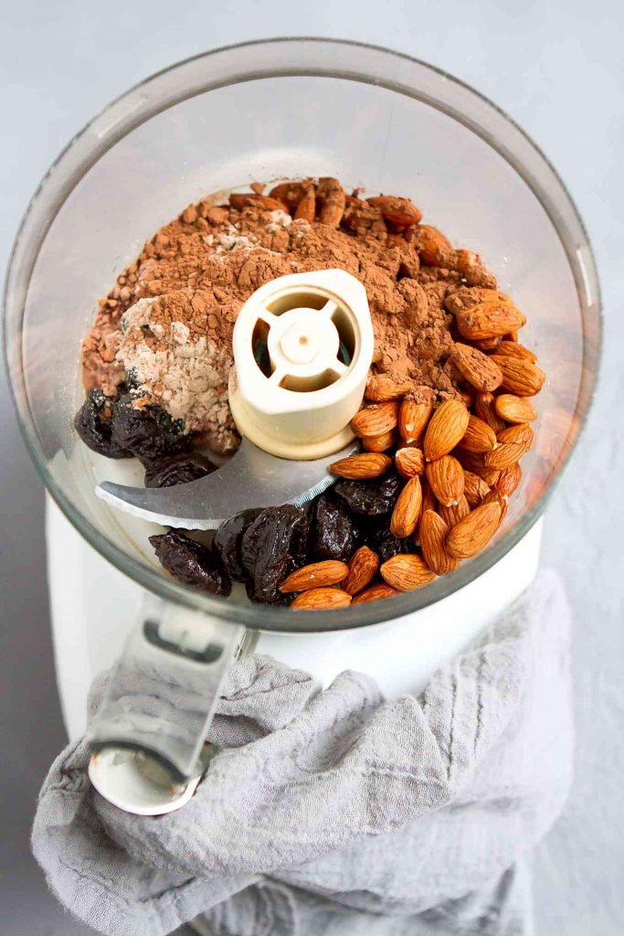 Almonds, prunes and chocolate protein powder in a food processor.