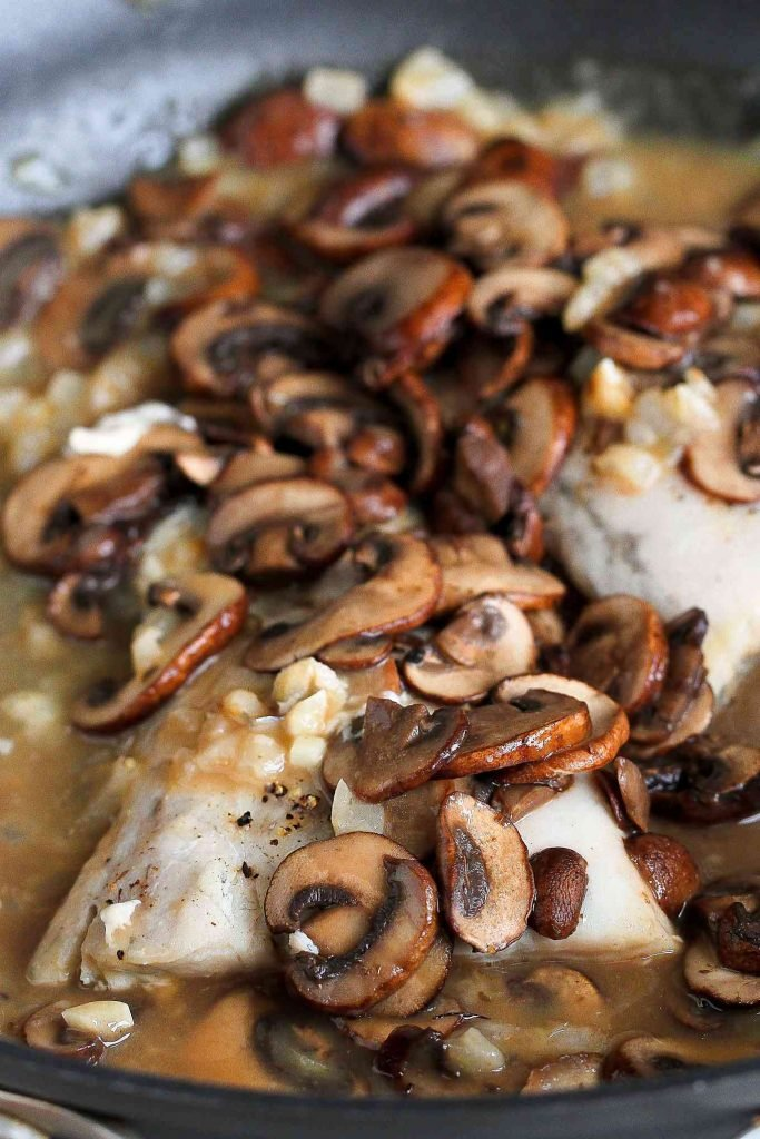 Sauteed sliced mushrooms on fish fillets, simmering in a marsala sauce.