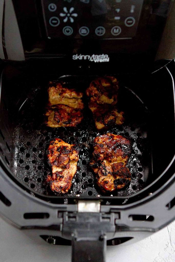 Glazed chicken thighs in the basket of an air fryer.