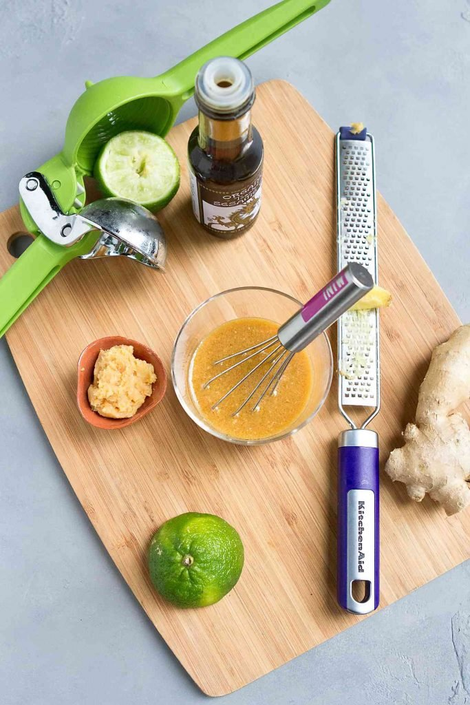 Ingredients for miso sesame ginger dressing on a bamboo cutting board