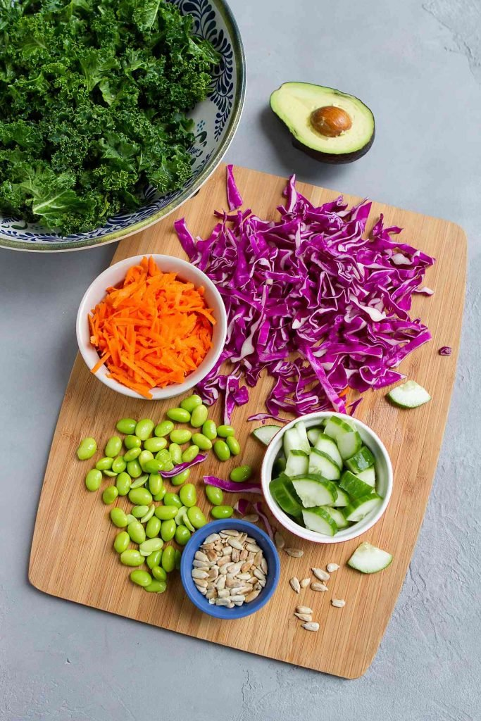 Kale, cabbage, grated carrots, cucumber, edamame, avocado, sunflower seeds and dressing on a bamboo cutting board
