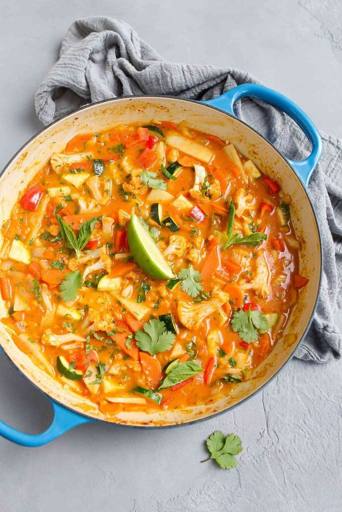 Vegan Thai red curry with cauliflower in a large skillet with blue handles.