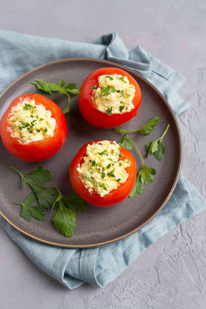 Serve this easy stuffed tomato recipe for lunch or brunch. Stuffing them with a light egg salad is a great way to use up hard boiled eggs! 125 calories and 1 Weight Watchers SP | Healthy | Vegetarian | Celery | Recipe | Tomato | Low Carb | Easy | Easter #stuffedtomatoes #easterrecipes #brunch #weightwatchers #eggsalad #vegetarianbrunch