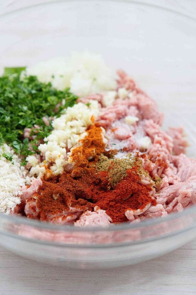 Ground turkey, breadcrumbs and spices in a glass bowl