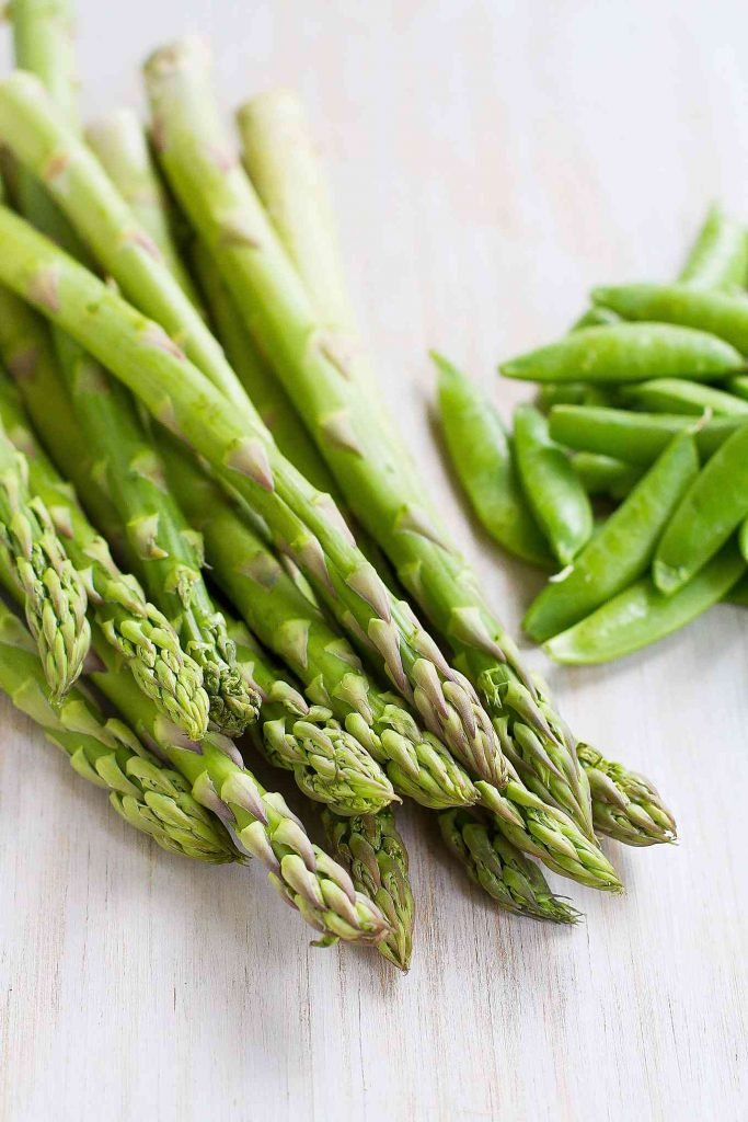 Asparagus spears and sugar snap peas on a white surface.