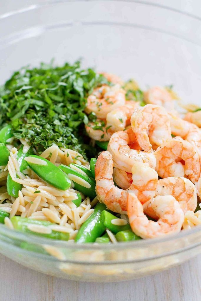 Cooked shrimp, orzo pasta, fresh herbs and snap peas in a glass bowl.