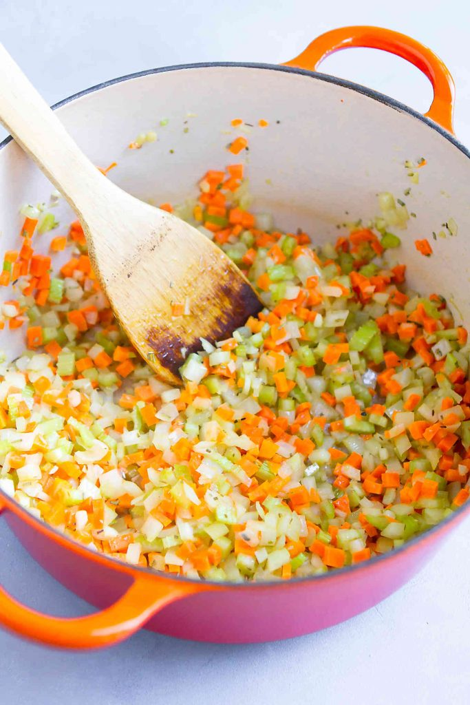 Diced onion, celery, carrot, garlic and rosemary in a large orange saucepan