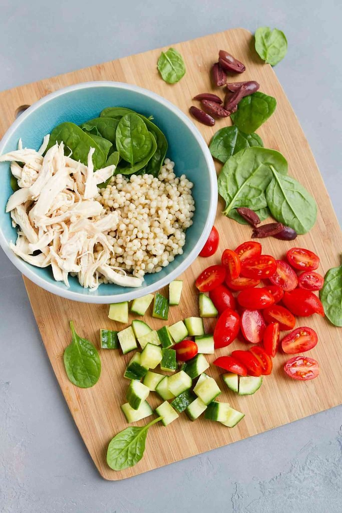 Chicken and Israeli couscous in a blue bowl. Tomatoes, cucumbers and olives on a bamboo cutting board.