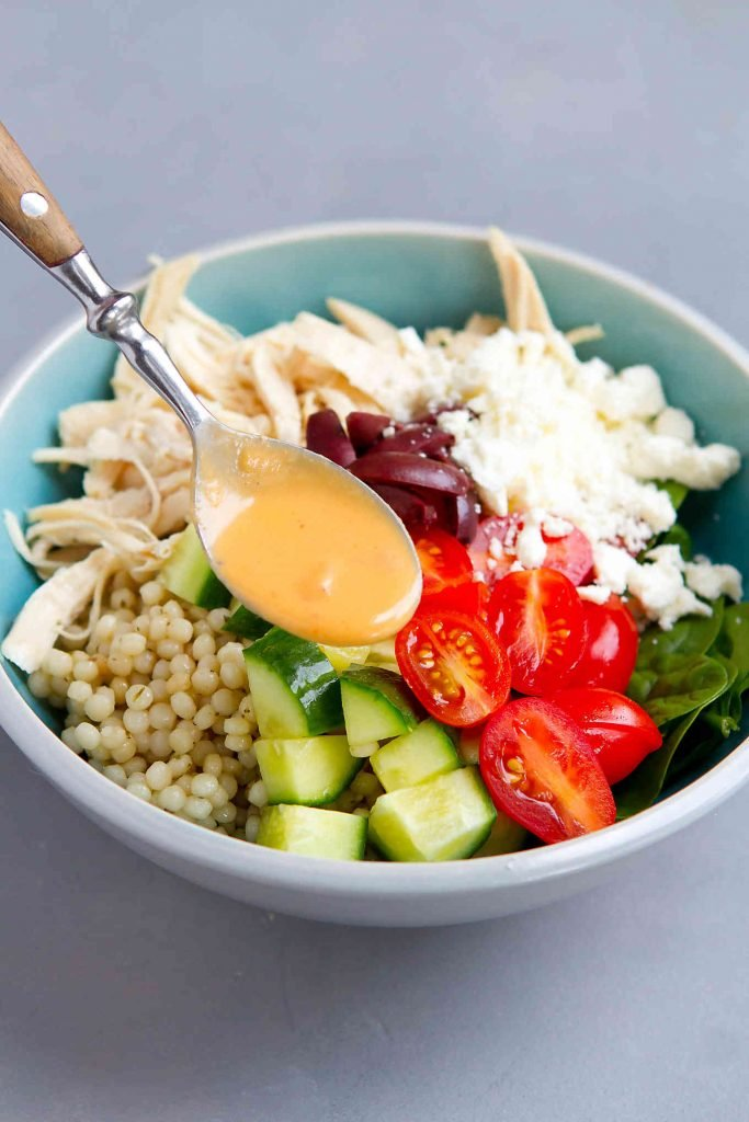 Drizzling hummus dressing over a salad.