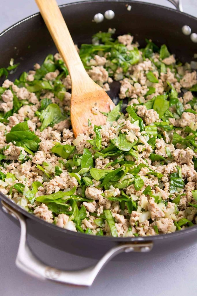 Ground turkey and spinach leaves in a large nonstick skillet