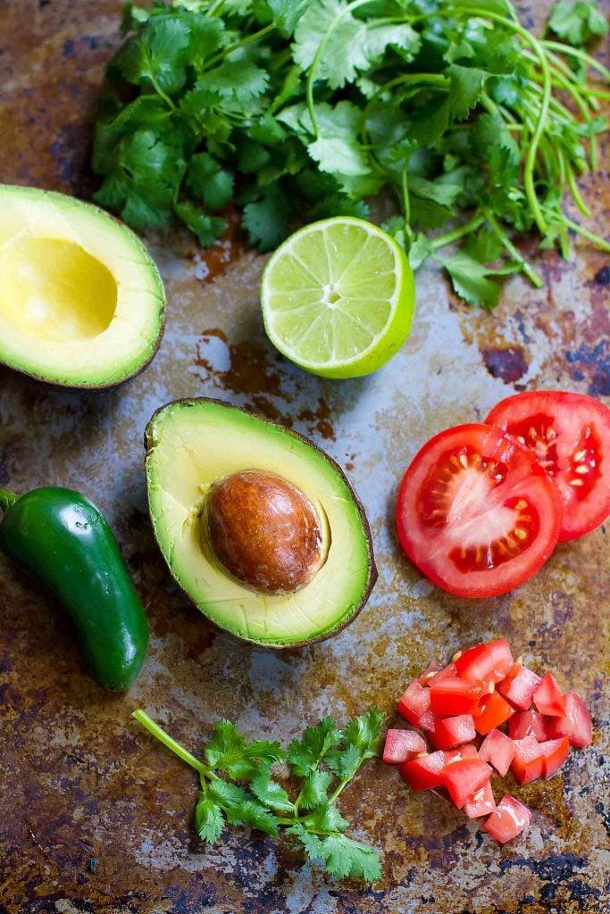 Avocado salsa ingredients on baking sheet.