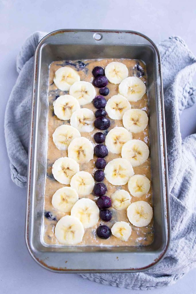 Banana bread batter in a loaf pan, topped with blueberries and banana slices.