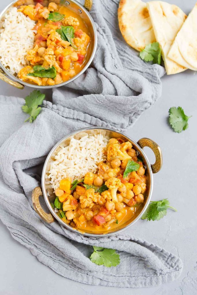 Pull out the crockpot for this vegan coconut curry recipe. Packed with sweet potatoes, cauliflower and chickpeas for a hearty, satisfying meal. 181 calories and 2 Weight Watchers Freestyle SP | Plant Based | Vegetarian | Sweet Potato | Coconut | Easy | Recipes | Slow Cooker | Healthy | Spinach and #plantbased #vegancurryrecipes #chickpeacurry #vegetablecurry #weightwatchers #smartpoints
