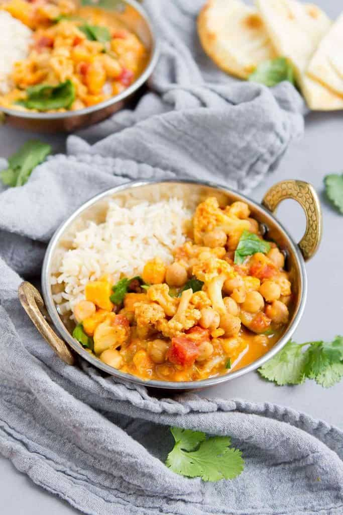 This slow cooker vegan chickpea curry recipe has been a long-time favorite in our house. It's packed with nutrients and flavor! Plus, it's a breeze to make. 181 calories and 2 Weight Watchers Freestyle SP | Plant Based | Vegetarian | Sweet Potato | Cauliflower | Coconut | Easy | Recipes | Crockpot | Healthy | Spinach and #plantbased #vegancurryrecipes #chickpeacurry #vegetablecurry #weightwatchers #smartpoints
