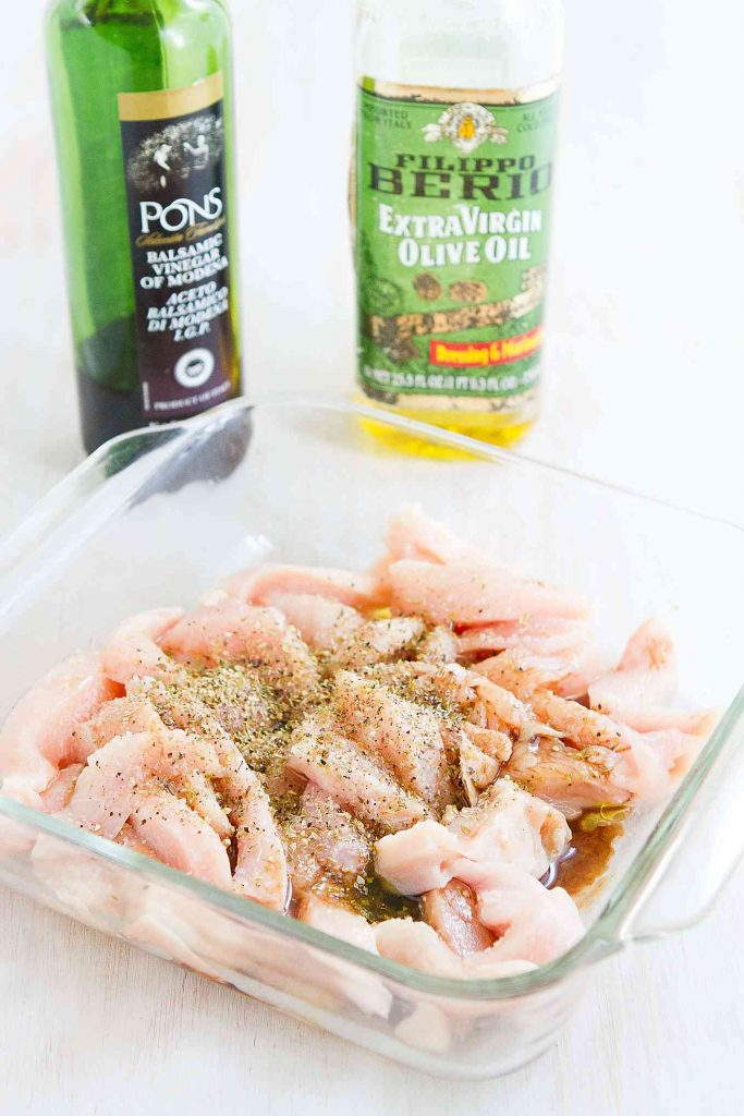 Chopped chicken breast in a glass container, with olive oil and balsamic vinegar bottles