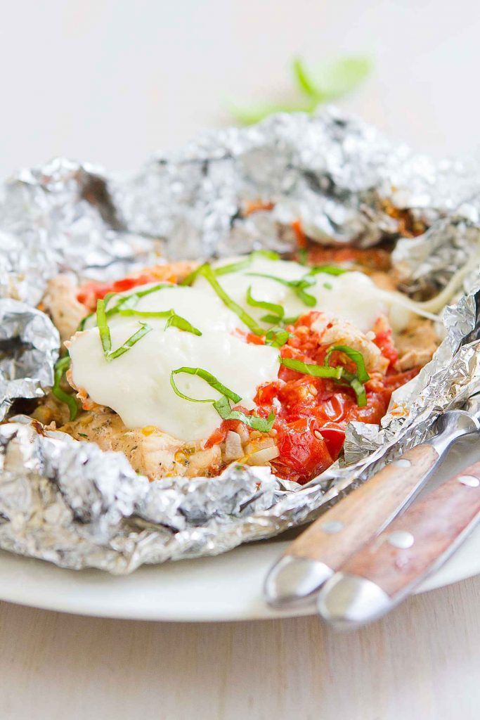 Cooked chicken, mozzarella cheese and basil sitting on foil.