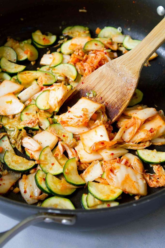 Sauteed zucchini slices with cabbage kimchi in a large black skillet