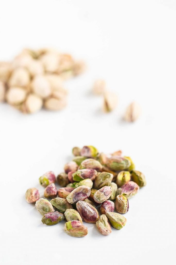 Shelled pistachios on a white background.