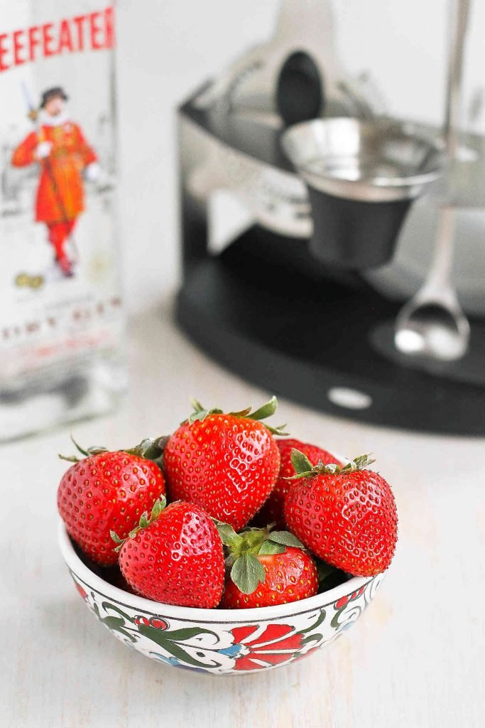 Bowl of strawberries with a bottle of Beefeater gin and bar tools.