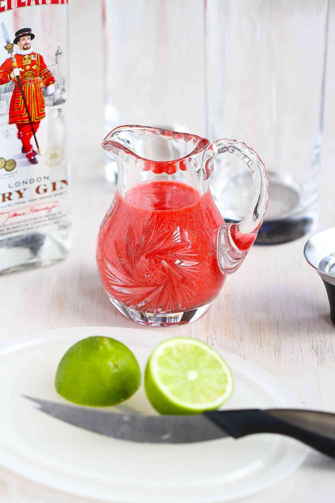 Small glass pitcher filled with strawberry puree, plus a cut lime, a bottle of gin and two empty Collins glasses.