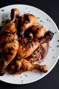 Grilled chicken drumsticks, sprinkled with parsley on a white plate.