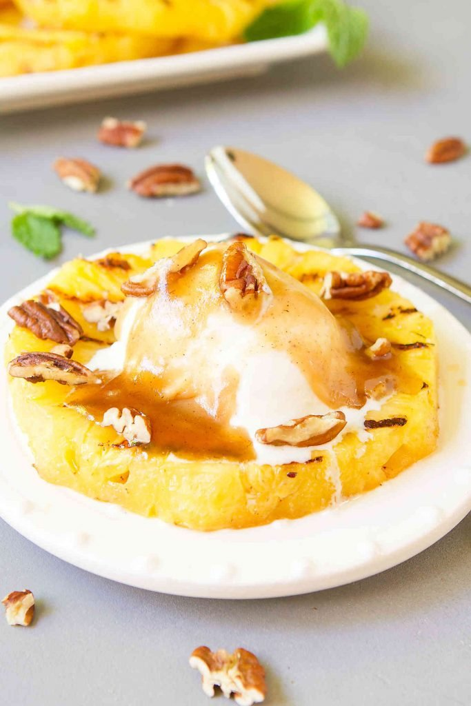 Grilled pineapple slice, topped with frozen yogurt and brown sauce on a white plate with mint leaf on side.