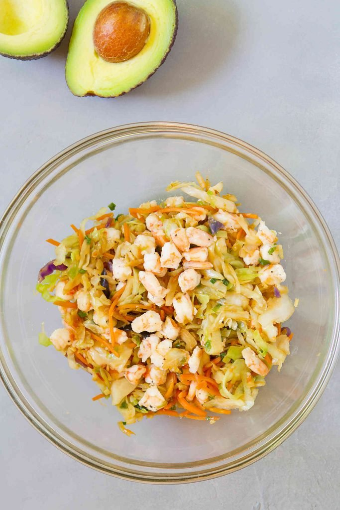 Cooked shrimp and cabbage mix in a glass bowl