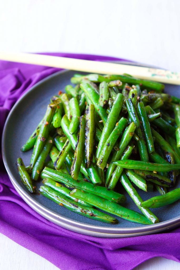 Cooked green beans and chopsticks on a dark gray plate, resting on a purple napkin.