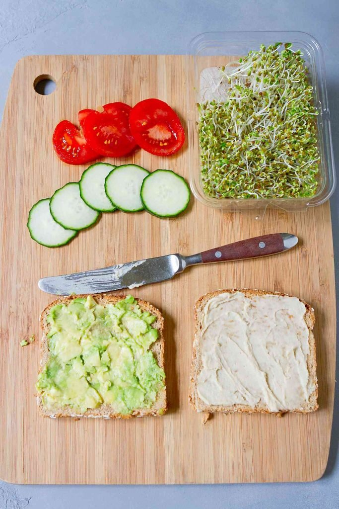 Two slices of bread, topped with hummus and avocado on a cutting board. Plus, sliced tomato and cucumber, and broccoli sprouts.