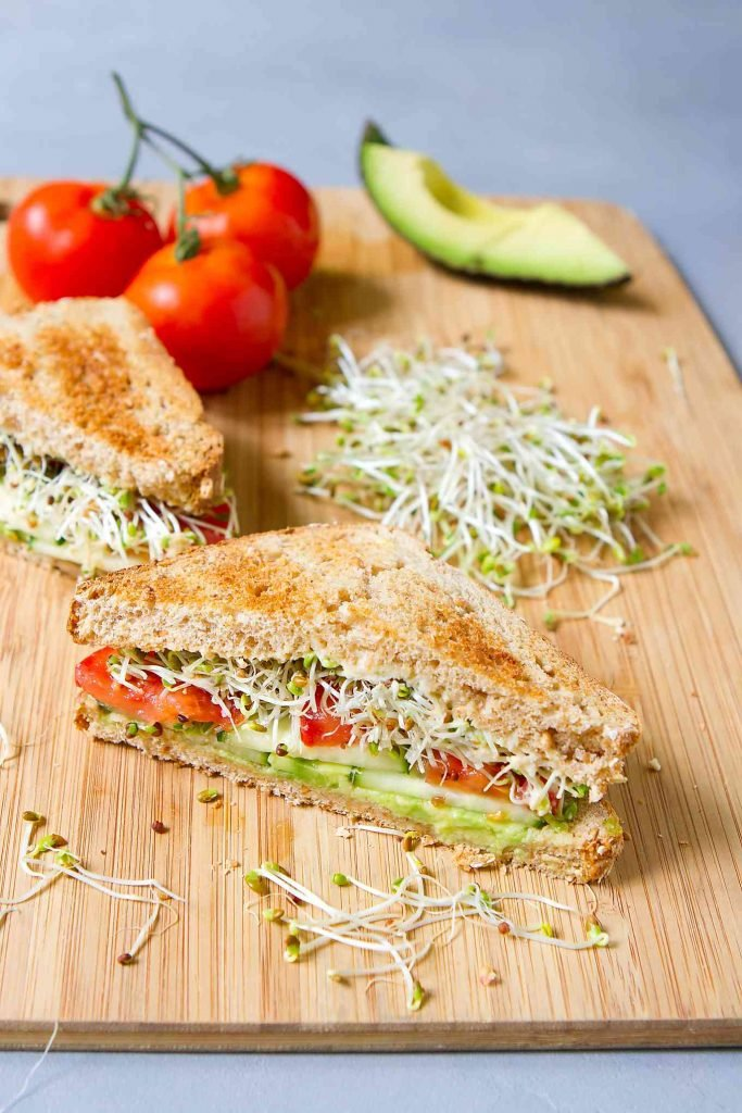 Two ssandwich halves, filled with avocado, cucumber, tomato and sprouts. Tomatoes and avocado in the background.