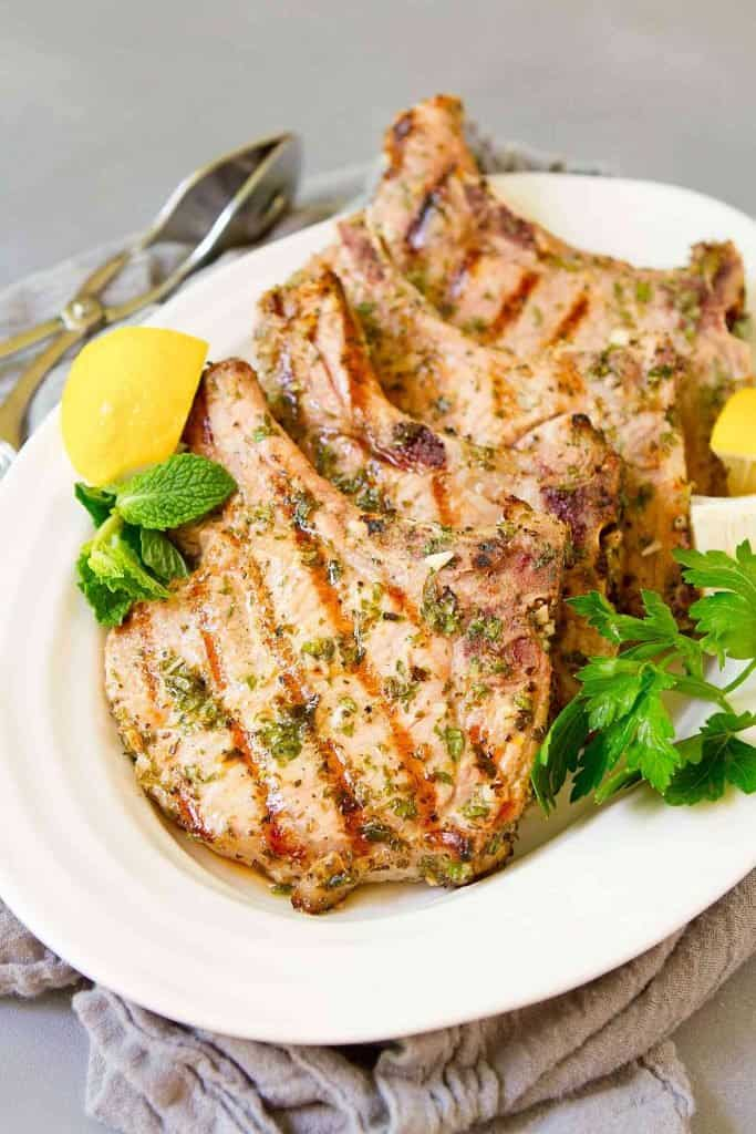 Grilled pork chops and lemon wedges on a white plate.