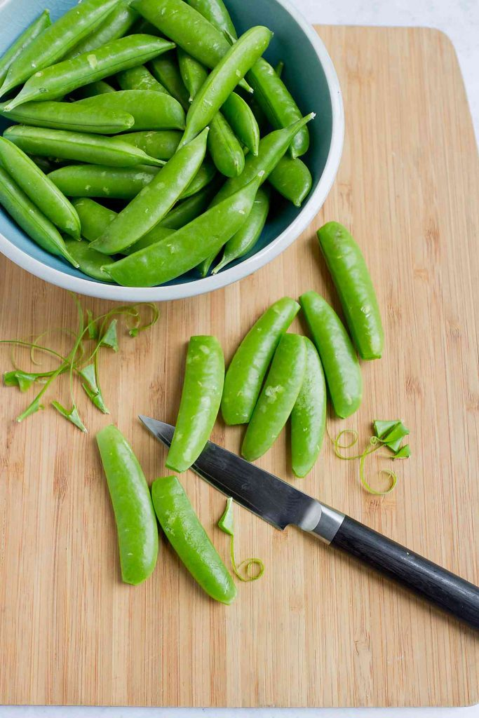 A bowl of snap peas and loose pods on a cutting board with a knife.