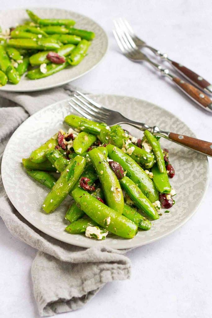 Sauteed sugar snap peas with feta and olives on two gray plates.
