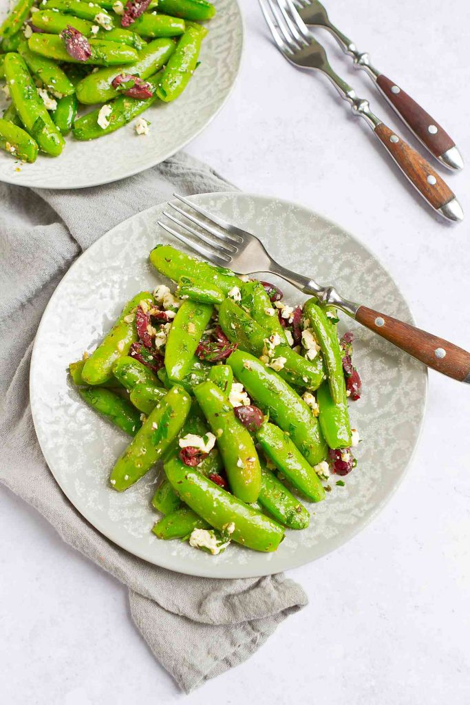 Overhead photo of sauteed sugar snap peas with feta and olives on two gray plates.