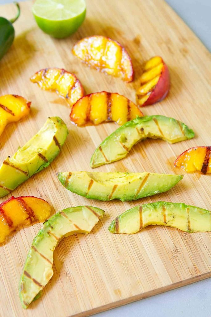 Slices of grilled avocado and grilled peach on a bamboo cutting board.