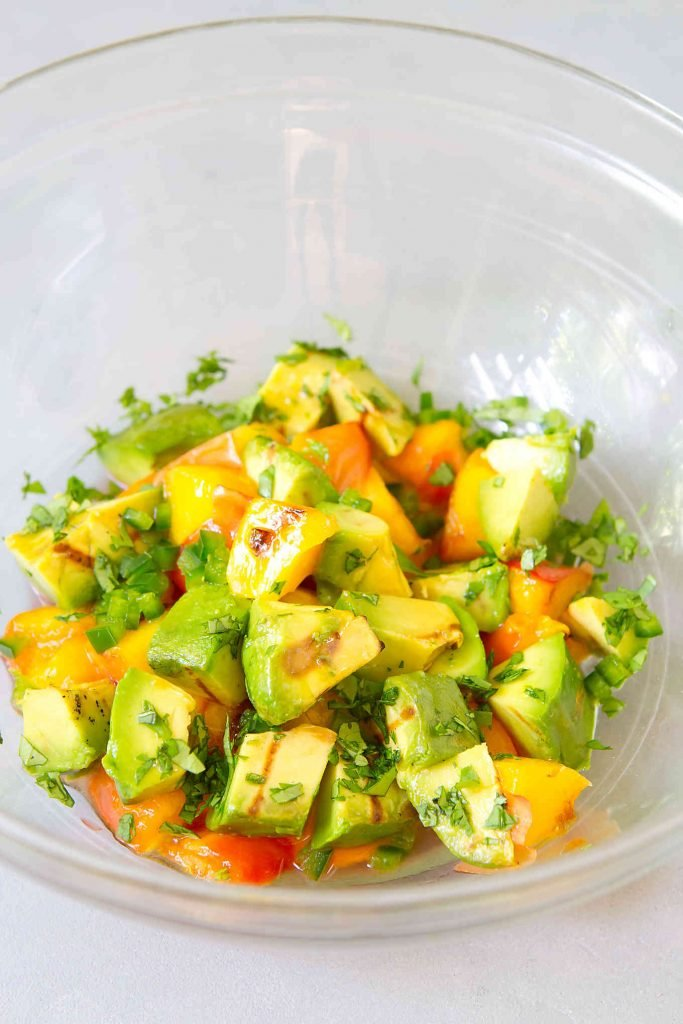 Chunks of grilled avocado, grilled peach and cilantro in a glass bowl.