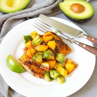Grilled fish with avocado peach salsa on a white plate, plus two half avocados in background.