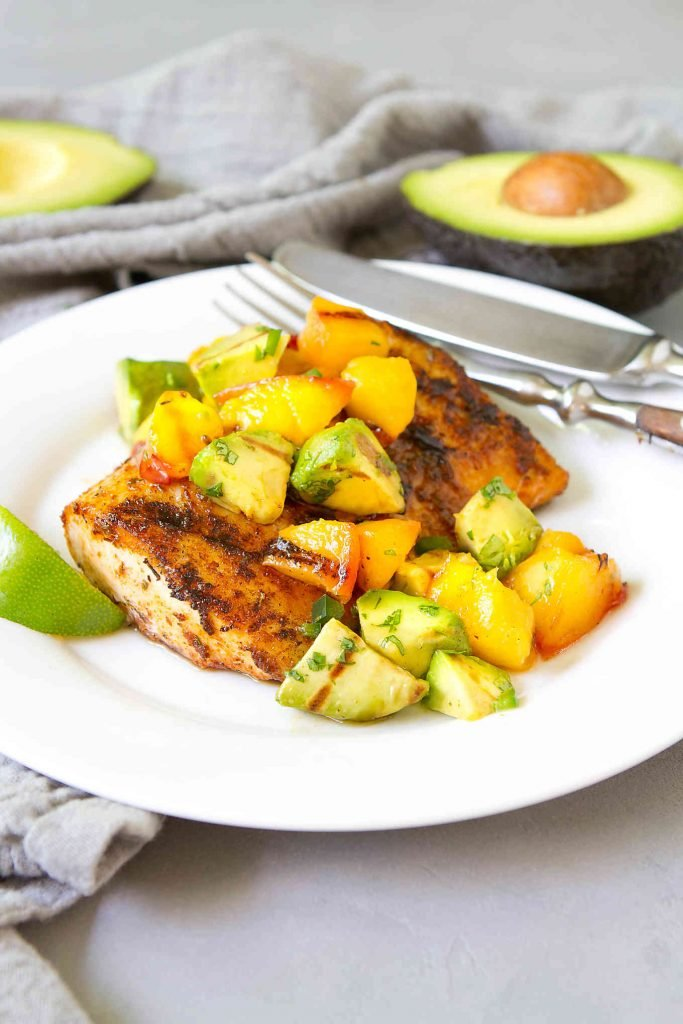 Grilled mahi mahi with avocado peach salsa on a white plate, plus two half avocados in background.
