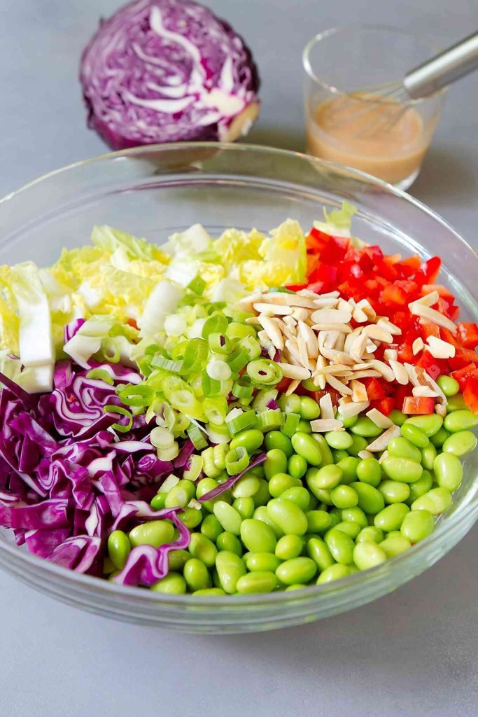 Chopped green and red cabbage, edamame, green onion and bell pepper and slivered almonds in a large glass bowl.