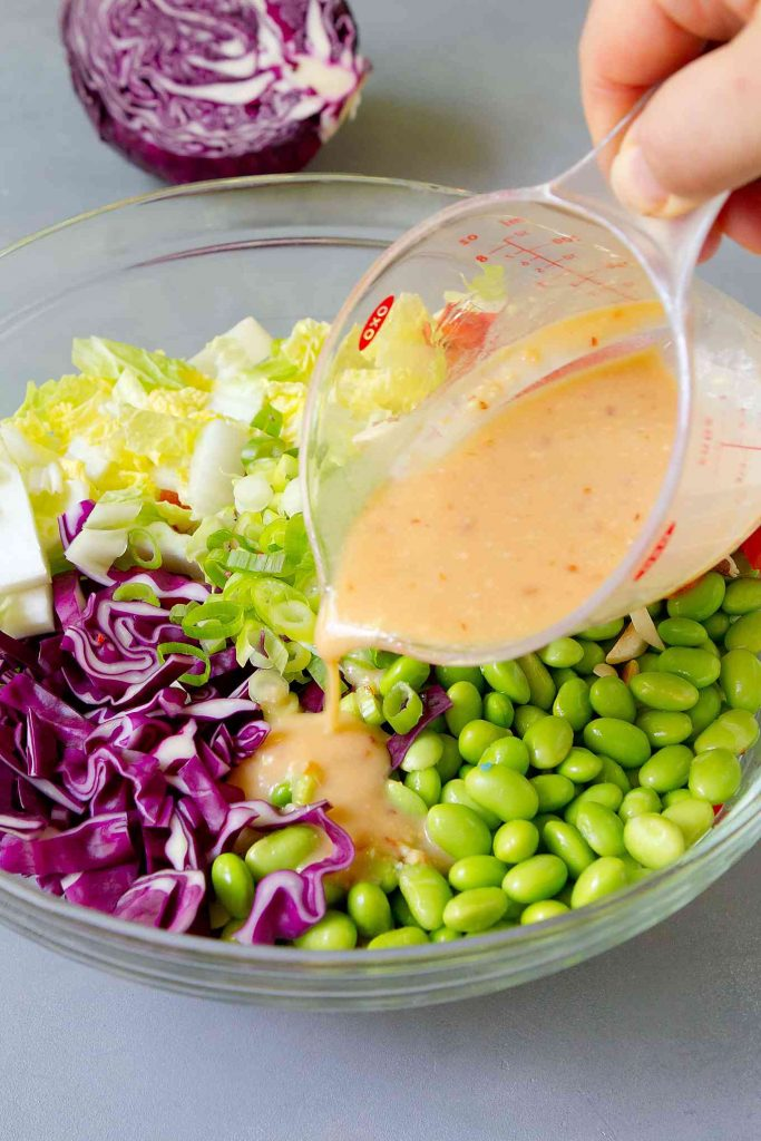 Pouring miso dressing out of a measuring cup into a slaw with edamame.