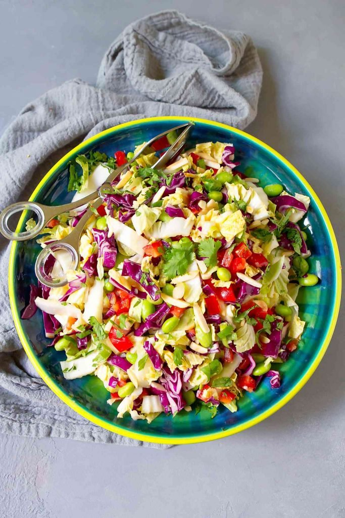 Slaw with green and red cabbage, bell pepper, edamame, cilantro and almonds in a blue-green bowl, on a gray napkin.