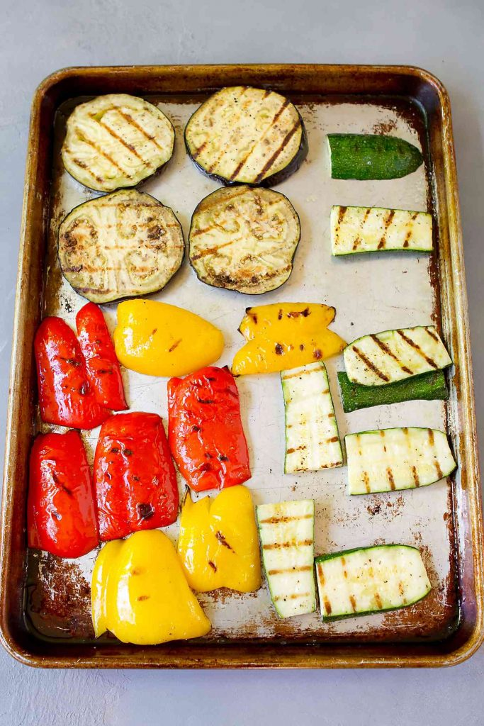 Eggplant and zucchini slices, red and yellow bell pepper quarters on a baking sheet.