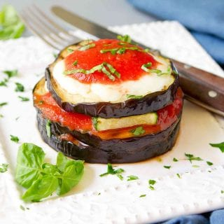 Stacks of grilled eggplant, zucchini, cheese and tomato sauce on white plate with basil.