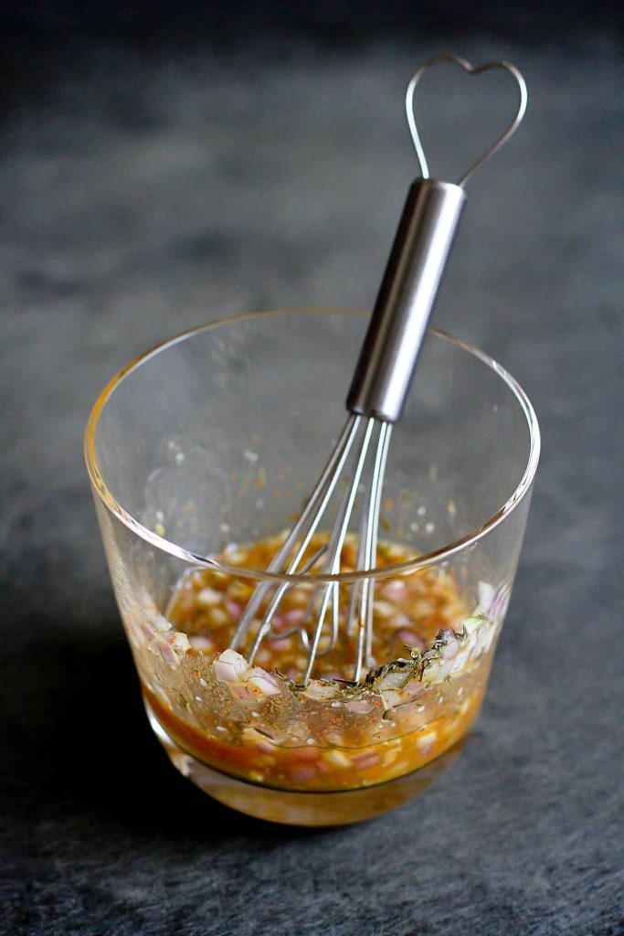 Mixture of mustard, maple syrup and herbs in a glass, with a whisk.